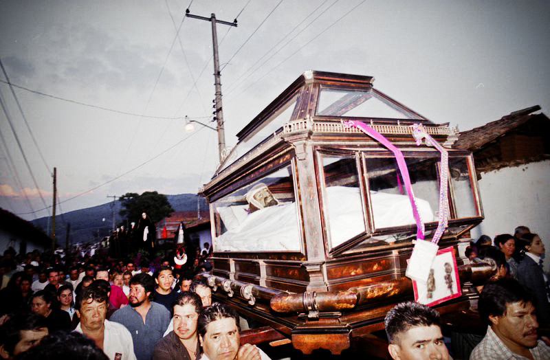 A statue of Jesus Christ in a glass coffin carried by many people during a procession.