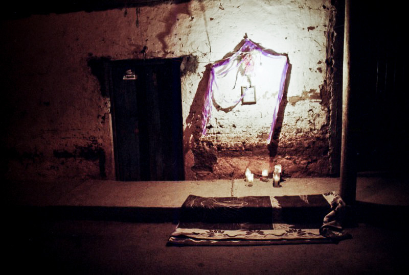 One of the prayer station lit by a bare bulb and decorated with purple streamers.