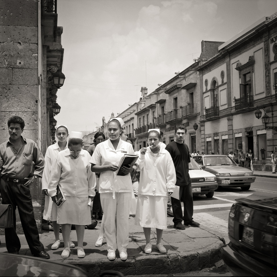 A group of nurses waiting to cross a busy street in Morelia, Mexico.