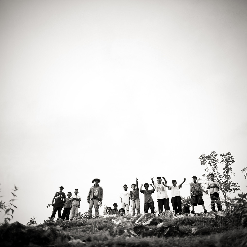 A group of Kids and an old man posing on a top of a hill in rural Mexican village.
