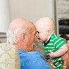 A grandfather holds his grandson as they look at each other