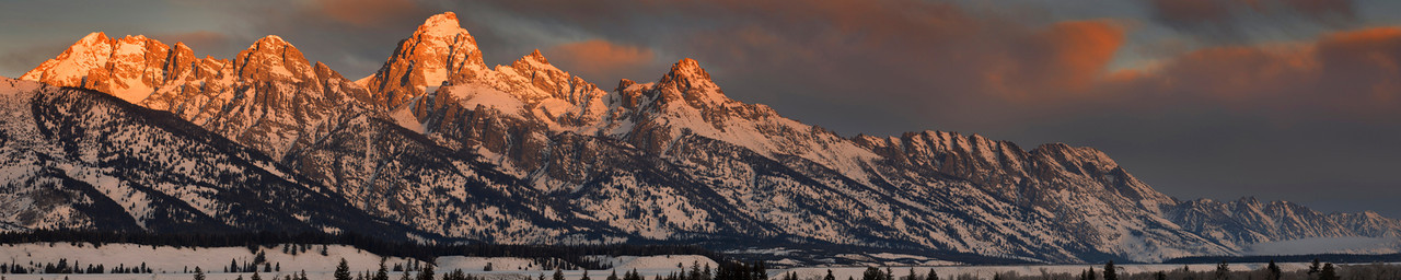 Dawn of Winter, Jackson - Wyoming<br /> <br /> The morning light brings both color and heat to the summit pinnacles of the Grand Teton and its family of jagged granite spires. Here, in January, at just 4 degrees above zero, the air was crisp and clear;  moose strolled the sagebrush dotted plaines, and back-country skiers left their marks along the slopes of the 'Grand'.