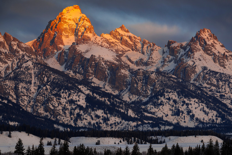 The Grand Teton - Wyoming  During the heart of winter, the Tetons wear a heavy white coat - hiding the boulders and scree, reflecting the sky, and holding the weight of springtime water for the wildflowers of summer and the hibernating animals of spring.
