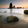 The Needles, Cannon Beach - Oregon<br /> <br /> Twice each day the black rocks surrounding The Needles are exposed to the open air and sunlight. Here, at low tide, the sun was slipping behind the Pacific Ocean, leaving a horizon of sunset colors, and the green mosses limp and thirsty.