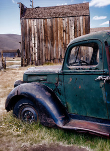 It Has Seen Better Days.      The cab of an old truck, sunk in the weeds of time, sits in its final resting spot adjacent the old rotting buildings of the ghost town.  Bodie, Ca