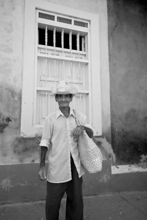 Cuban man in straw hat and bag in front of barree up window in Trinidad, Cuba