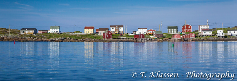 Reflections of salt box homes in the harbour at the fishing village of Tilting, Fogo Island, Newfoundland and Labrador, Canada.