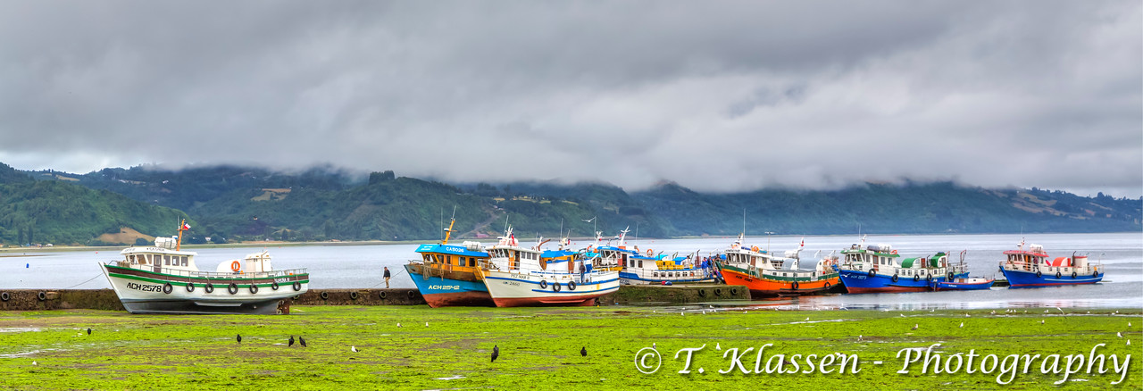 Fishing boats at low tide docked at the village of Achao, Chile, South America.