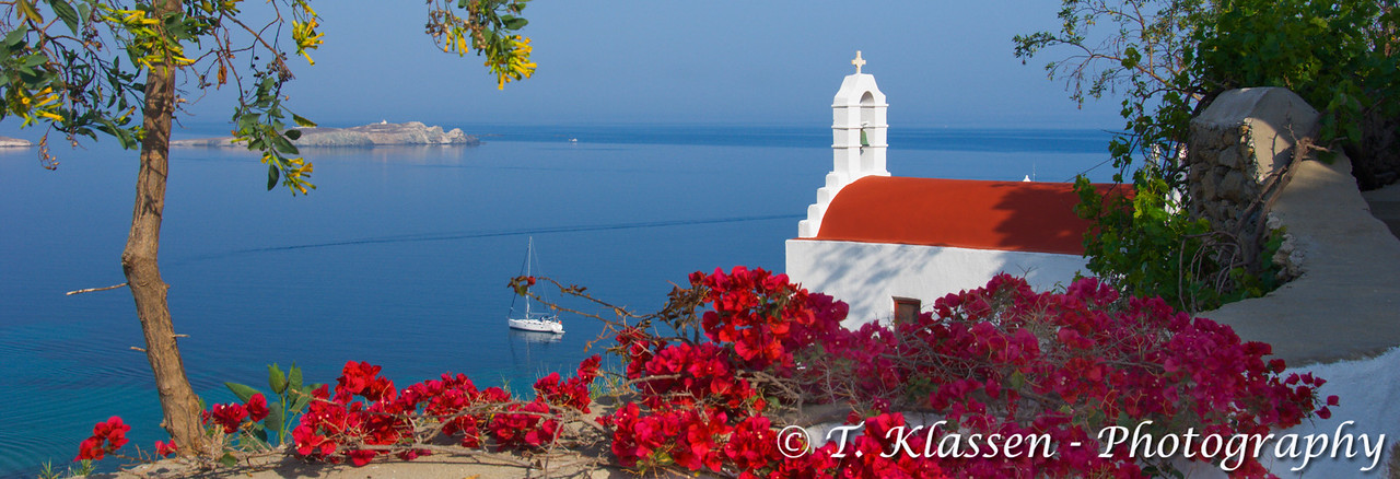 A typical Greek church with bougainvillea flowers in Hora or Mykonos town on the Island of Mykonos, Greece.