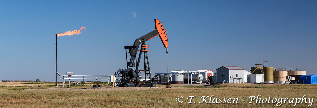An oil production pumper and flaring gas in the Bakken field near Stoughton, Saskatchewan, Canada.