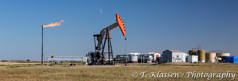 An oil production pumper and flaring gas in the Bakken field near Stoughton, Saskatchewan, Canada.