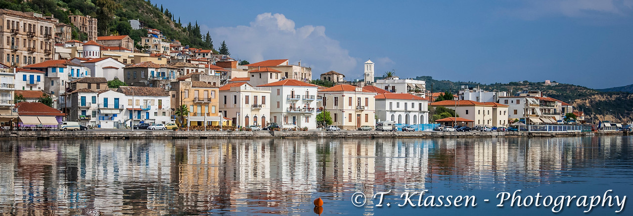 Pastel colored buildings on the waterfront and reflections in the harbor at the attractive fishing town of Githeo, Greece.