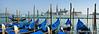 A row of blue gondolas  docked at shore in Venice, Italy.