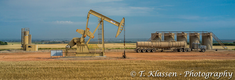 An oil pumper and a tanker truck in the Bakkan play oil fields near Williston, North Dakota, USA.