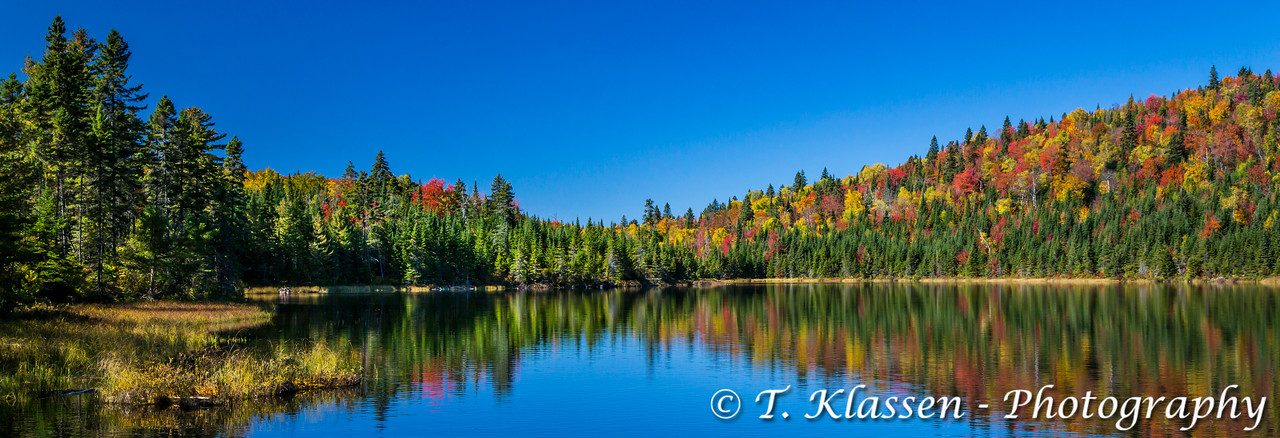 Brilliant fall foliage reflections in La Mauricie National Park, Quebec, Canada.