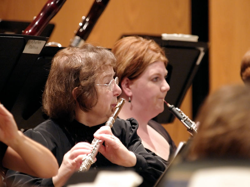 Floutist Jo Seidler has been a long time member of the woodwind section.  Next to her is oboist Yootha Neller.