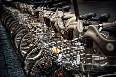 Bikes For Rent It's called Velib... and it's Paris' genius rent-a-bike program, brainchild of the mayor. For a few coins, you hop on a bike, ride it to wherever you need to be - and park that puppy in the undoubtedly nearby docking station.  Miss the last subway train at 1am? Rent a bike! Late night of clubbing, no taxis handy? Use the Velib! Don't want to have your own bike ripped off or worry about where to park it? Voila! A lovely rental bike is just waiting to roll to your destination.   How much does revenue does it pull in? I just read an article from 2007 that claimed $28 million for that year.   I love smart ideas.    ©Karen Hutton - Creative Commons (CC BY-NC 3.0)