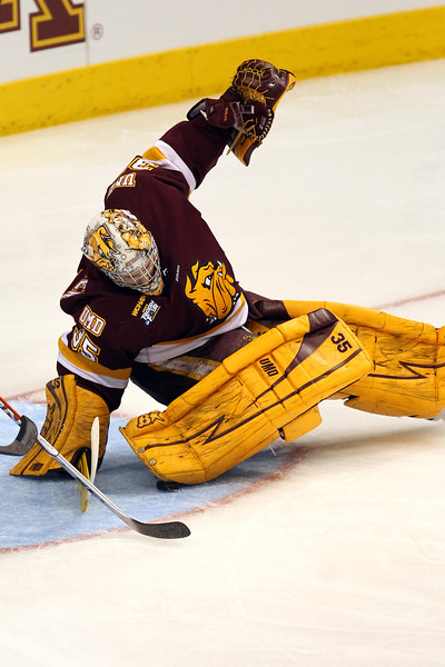 University of Minnesota Duluth Bulldogs goalie Kenny Reiter (35) pinches the puck in the first period of the NCAA Frozen Four between the University of Minnesota Bulldogs and the University of Michigan Wolverines at the Xcel Energy Center St, Paul, MN. Michigan led 1-0 at the end of the first period.