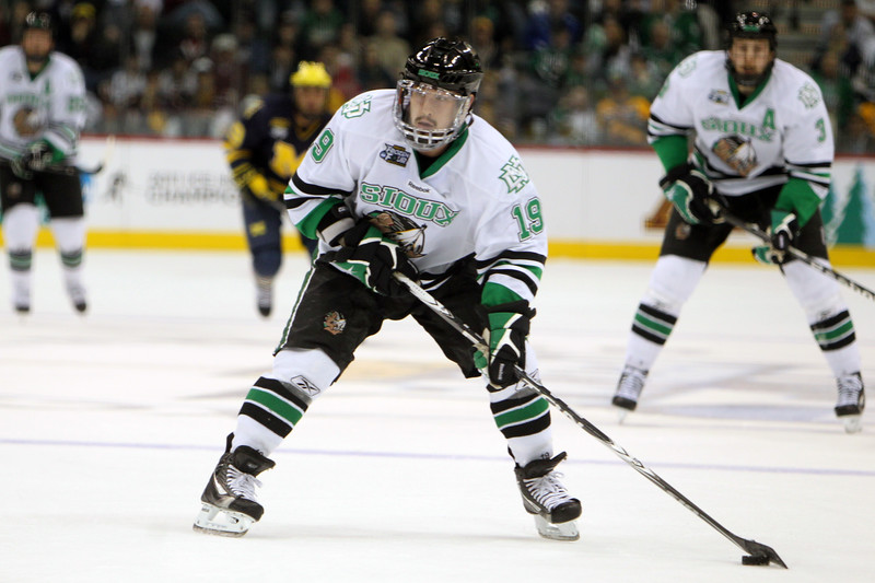 University of North Dakota Fighting Sioux forward Evan Trupp (19) tees up the puck in the second period of the NCAA Frozen Four between the University of Michigan Wolverines and the North Dakota Fighting Sioux at the Xcel Energy Center St, Paul, MN. The score remained 1-0 Michigan after two periods.