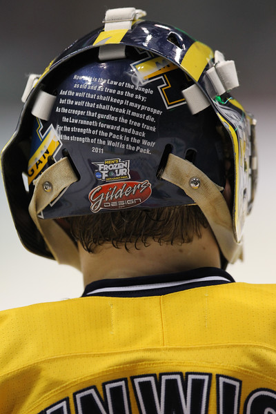 University of Michigan Wolverines goalie Shawn Hunwick (31) shows a his helmet at the NCAA Frozen Four championship game between the University of University of Minnesota Bulldogs and the University of Michigan Wolverines at the Xcel Energy Center St, Paul, MN. The game was tied 2-2 after two periods.