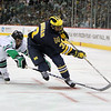 University of Michigan Wolverines forward Scooter Vaughan (3) extends to steer the puck against University of North Dakota Fighting Sioux defenseman Derek Forbort (4) in the third period of the NCAA Frozen Four between the University of Michigan Wolverines and the University of Minnesota Fighting Sioux at the Xcel Energy Center St, Paul, MN. Michigan wins the game 2-0 to advance to the championship game.