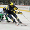 University of Michigan Wolverines forward Scooter Vaughan (3) advances the puck under heavy pressure in third period of the NCAA Frozen Four between the University of Michigan Wolverines and the University of Minnesota Fighting Sioux at the Xcel Energy Center St, Paul, MN. Michigan wins the game 2-0 to advance to the championship game.