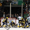 All eyes converge on the precious puck as it sits before University of Michigan Wolverines goalie Shawn Hunwick (31) and team in the final minutes in third period of the NCAA Frozen Four between the University of Michigan Wolverines and the University of Minnesota Fighting Sioux at the Xcel Energy Center St, Paul, MN. Michigan wins the game 2-0 to advance to the championship game.