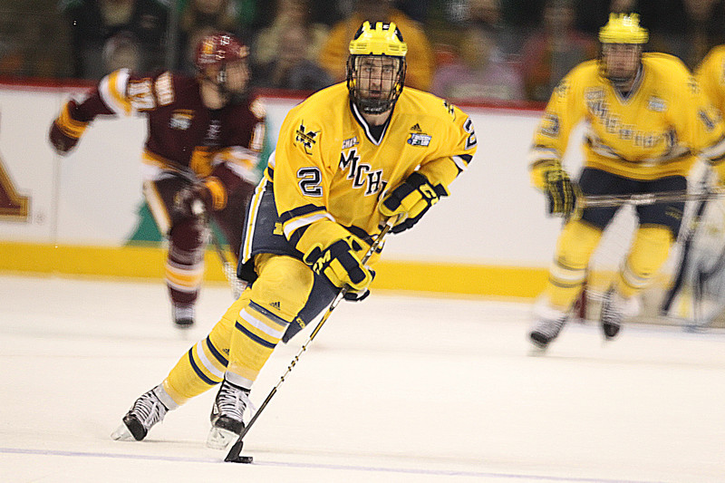 University of Michigan Wolverines defenseman Greg Pateryn (2) steers the puck from the Wolverine zone in the third period of the NCAA Frozen Four between the University of Minnesota Bulldogs and the University of Michigan Wolverines at the Xcel Energy Center St, Paul, MN. The score was tied 2-2 after three periods of regulation play.