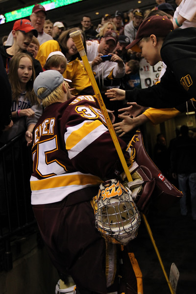University of Minnesota Duluth Bulldogs goalie Kenny Reiter (35)shares the celebration with fans at the NCAA Frozen Four between the University of Minnesota Bulldogs and the University of Michigan Wolverines at the Xcel Energy Center St, Paul, MN. UMD won the national title 3-2 in overtime.