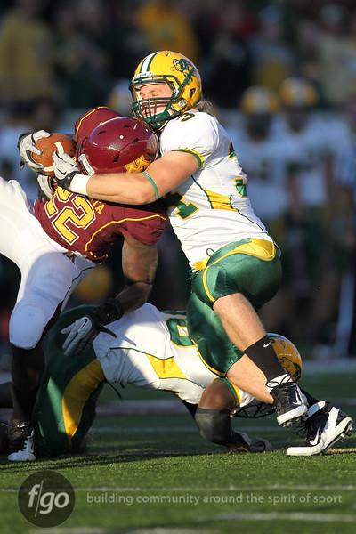 North Dakota State University Bison linebacker Grant Olson (34) wraps up University of Minnesota Gopher running back Duane Bennett (22) at the football game at the TCF Stadium in Minneapolis, MN.  North Dakota State won the game 37-24.