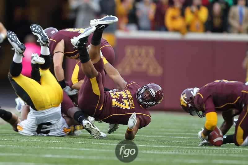 University of Minnesota Gophers linebacker Aaron Hill (57) and University of Iowa Hawkeyes running back Jason White (3) go head over heals on a Minnesota on-side kick in the fourth quarter of a football game against the University of Iowa Hawkeyes at TCF Stadium in Minneapolis, Minnesota. The on-side kick was recovered by Gophers safety Kim Royston (3). The Gophers won the game 22-21.