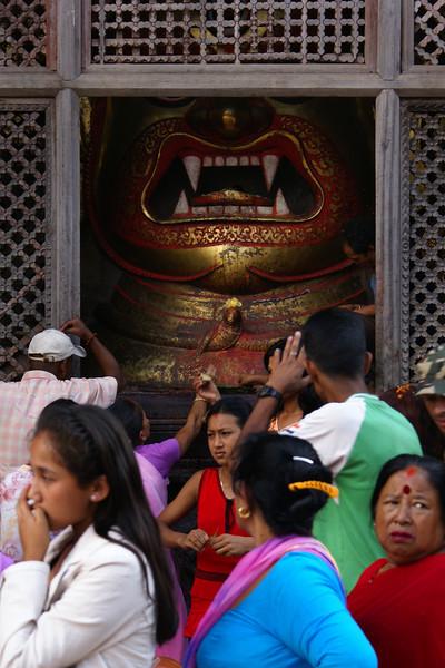 WORSHIPPING AT THE SETO BHAIRAB [WHITE DEMON]. GOLDEN MASK. DURBAR SQUARE. DASHAIN FESTIVAL. KATHMANDU.