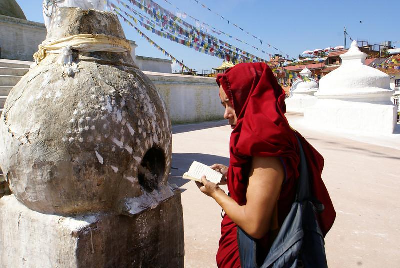 MONK PRAYING AT THE BODNATH STUPA. KATHMANDU.