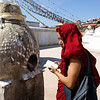 MONK PRAYING AT THE BODNATH STUPA. KATHMANDU.