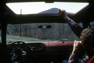 "Nancy reaches from Plymouth Trailduster coming down Little Mountain, West Shokan, NY (ca 1975) Note 8-track of Traffic's ""When the Eagle Flies"" in dash."