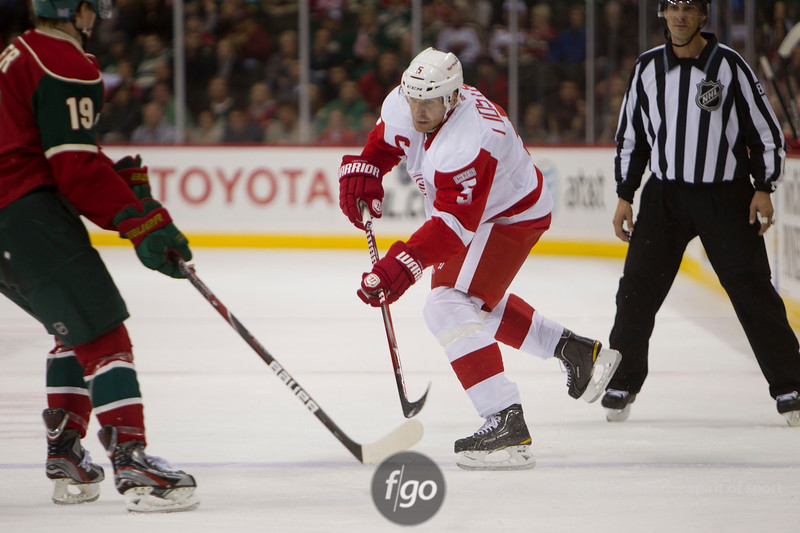Detroit Red Wing captain defenseman Nicklas Lindstrom (5) passes the puck past Minnesota Wild right winger Brett Bulmer (19) in the hockey game between the Detroit Red Wings and the Minnesota Wild at the Xcel Energy Center in St. Paul, Minnesota. The Red Wings won the game 3-2 in overtime.