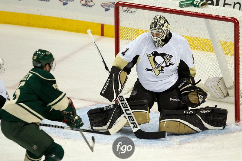 Pittsburgh Penguins goalie Brent Johnson (1) eyes a shot on goal by Minnesota Wild left wing Dany Heatley (15) in the first period of a hockey game between the Penguins and Wild at the Xcel Energy Center in St. Paul Minnesota. The Penguins won the game 4-2.