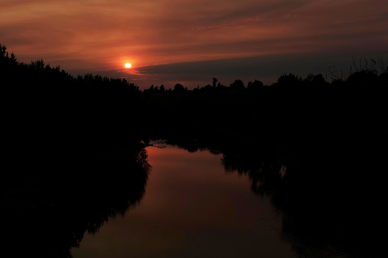 The Spokane River is seen, as the sun sets behind clouds and appears warm due to wildfire smoke, from the Greene Street Bridge, Sunday, Aug. 15, 2021, in Spokane, Wash. Although the air quality has improved, wildfire smoke is still visible in the sky. (Young Kwak)