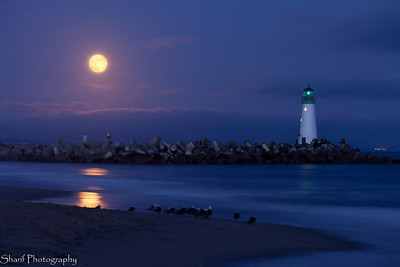 The lighthouse at the Santa Cruz harbor under a full moon.