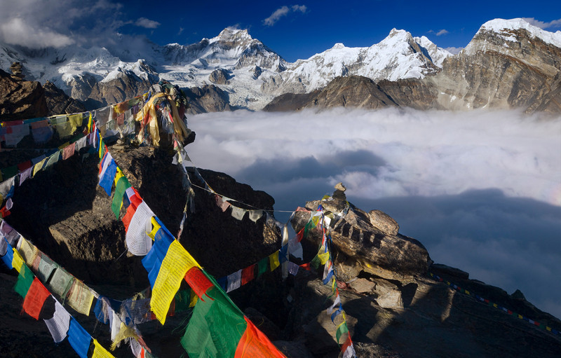 Prayer Flags on Gokyo Ri - Nepal<br /> <br /> Buddhist prayers flutter skyward, from the block-printed prayer flags left by so many travelers to this high place. Partially veiled in the background is the legendary south face of Cho Oyu, the sixth highest mountain in the world at 8,201 meters. In 1983 Reinhold Messner, Hans Kammerlander, and Michl Dacherand completed the first ascent of this extraordinary wall.