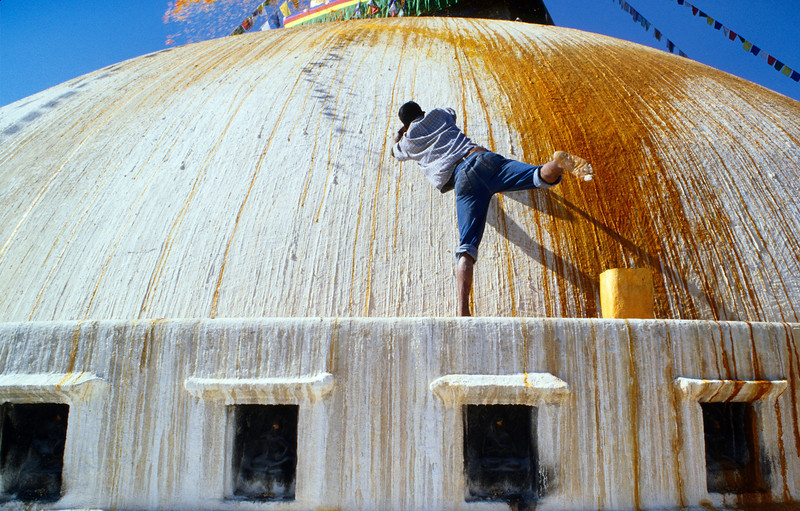 Saffron Water, Kathmandu - Nepal<br /> <br /> As part of Buddhist ritual, a young man throws great arcs of yellow saffron water onto the great dome of Bodhnath, the largest Buddhist Stupa in the world.