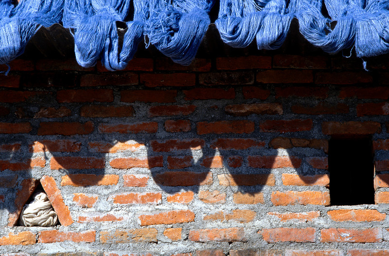Blue Yarn, Kathmandu - Nepal<br /> <br /> Freshly dyed, hand spun wool yarn, hangs from the roof of a small home in Kathmandu. With a few days of sun and a light breeze, the yarn will be ready for weaving.