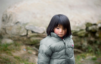 Namche Girl - Nepal  Children of the Himalayan village of Namche bundle up with down jackets against the evening cold. Increasingly, the Sherpa children have taken on the function of western fashion over the local warmth of wool and fur.