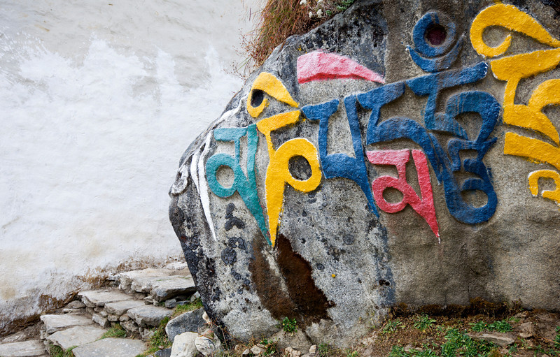 Mani Stone and Stairs, Tengboche - Nepal<br /> <br /> A huge boulder, painstakingly carved with the Tibetan Buddhist prayer - 'Om Mani Padme Hum', guards a worn flight of stairs as it dives up and behind the Tengboche Monastary.