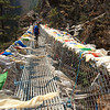 Bridges and Prayers, Khumbu Valley - Nepal<br /> <br /> In 1999, most of the bridges in this valley were still constructed of metal cable and wooden planks, giving cause for a concerned pace across the ill-alligned and sometime missing foot boards. Now, however, almost all have been painstakingly replaced with these stronger welded aluminum bridges. But even these move and sway during crossing, and two-way traffic - particularly yak traffic - elevates the tension of everyone on board.