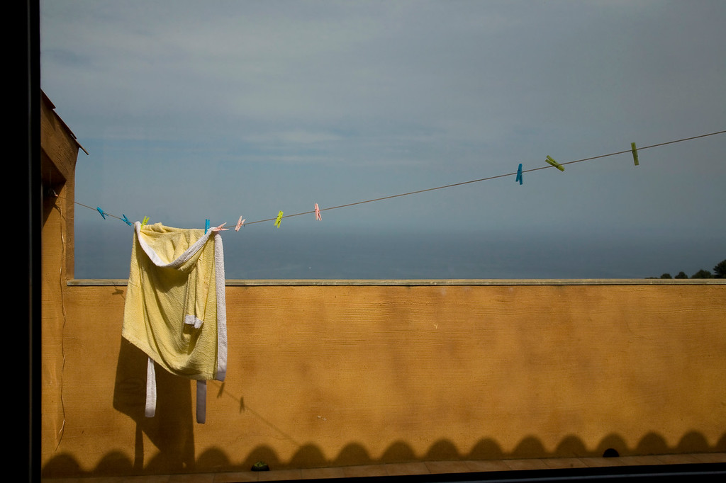 Yellow robe hanging on the balcony. Sea and blue sky in the background.