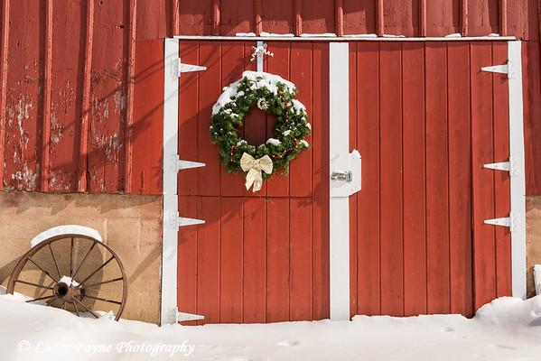Wreath hanging on  a red barn with freshly fallen snow on a farm near Edgewood in Northeast Iowa.<br /> <br /> February 26, 2015