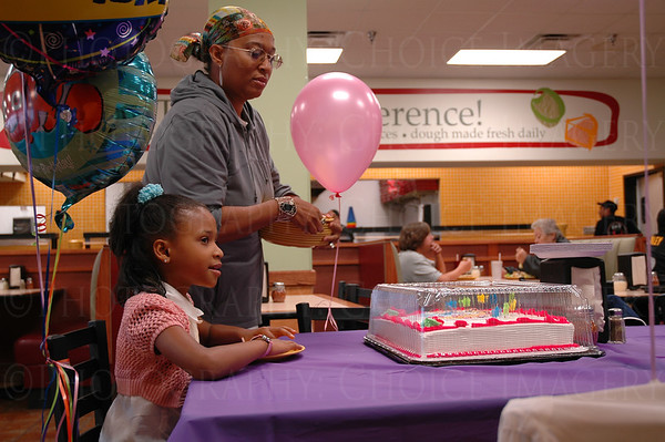 Birthday girl sits at head of table, while mother sets it up
