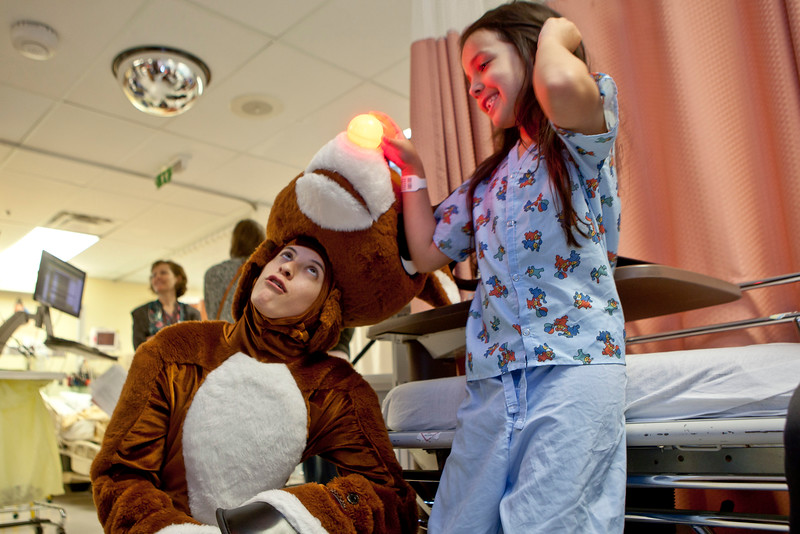 "Steyce Garcia, 6 smiles while turning on Rudolph's nose. Rudolph is played by Lexy Baeza, a Los Angeles performer in the Bushnell's, ""Rudolph the Red Nosed Reindeer: The Musical."" Performers entertained patients and families at Connecticut Children's Medical Center in Hartford, Friday afternoon. January 7, 2015."