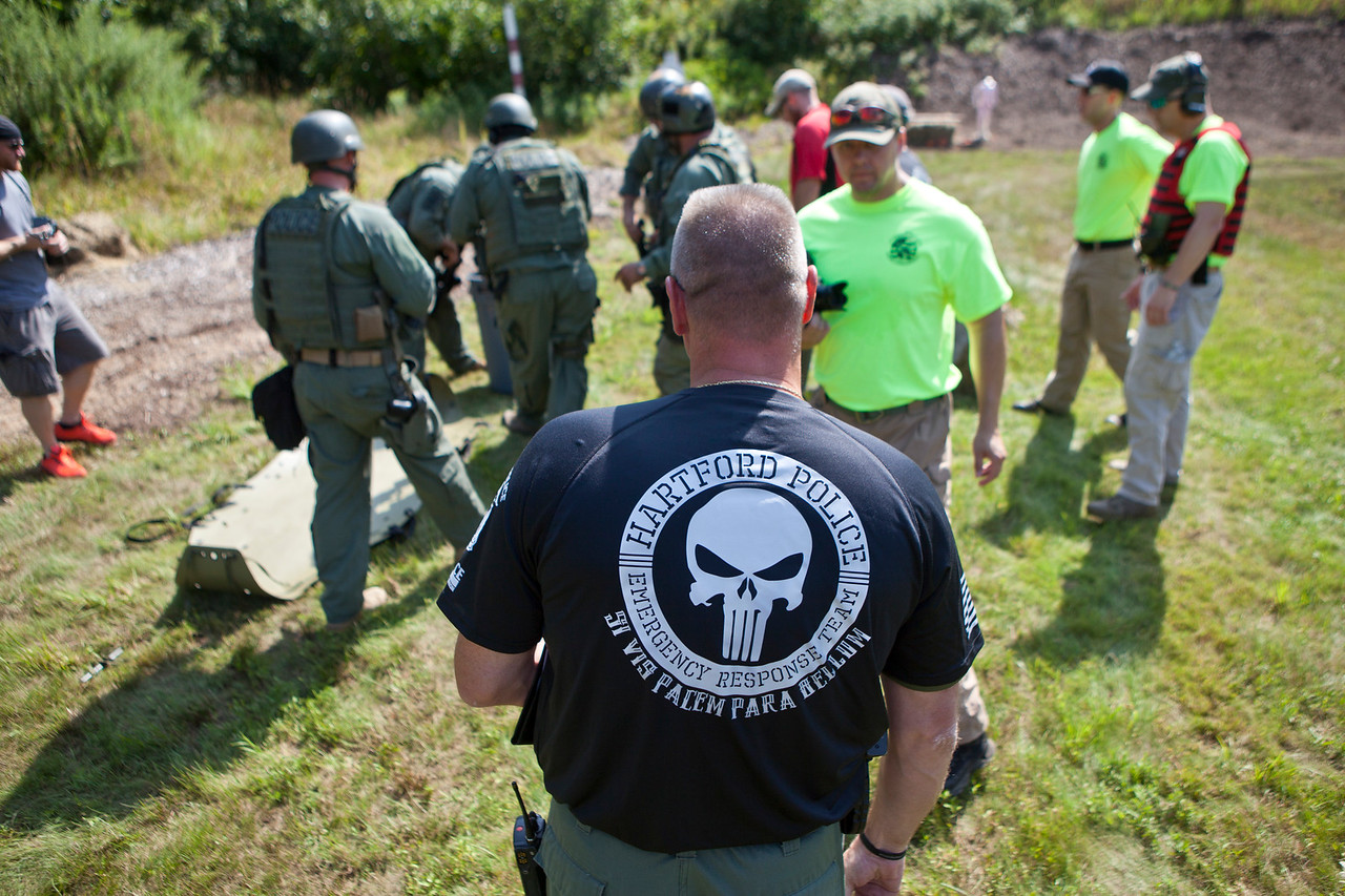 "Hartford Police Lieutenant, Michael Manson, center, stands with the officers at the Metacon Gun Club in Simsbury which hosted the 10th Annual CT SWAT Challenge. ""Si vis pacem para bellum""  is a Latin adage directly translated as, ""If you want peace, prepare for war"" but is often interpreted as ""peace through strength."" Police Departments and Military Units from several states participated in numerous challenges including the officer rescue and hostage challenges."
